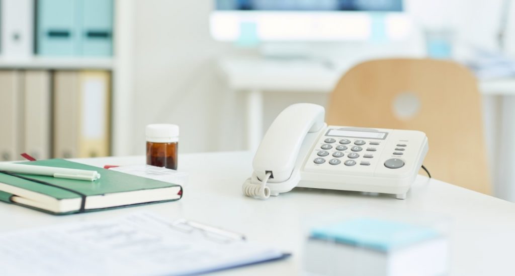 Background image of corded phone on empty table at workstation in clinic or hospital, copy space